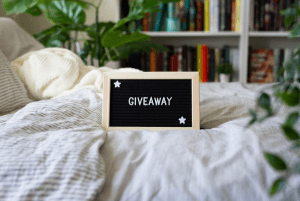 A board in front of a bookshelf that says Giveaway
