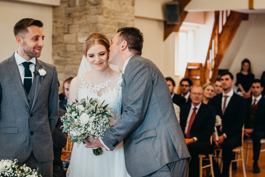 father of the bride kissing daughter in ceremony
