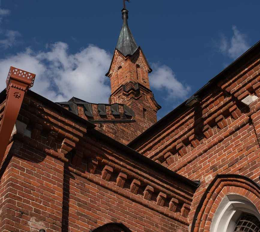 brown brick church under blue sky
