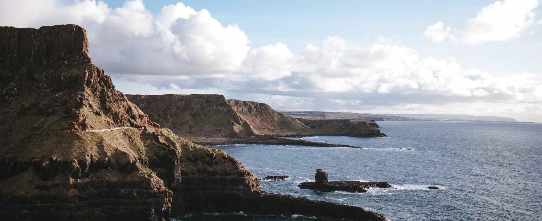 rocky coast against calm sea during sunny day
