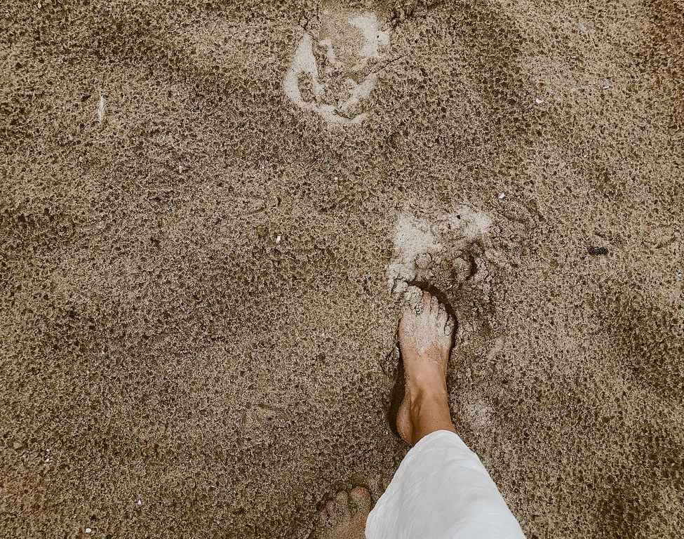 person walking on sand