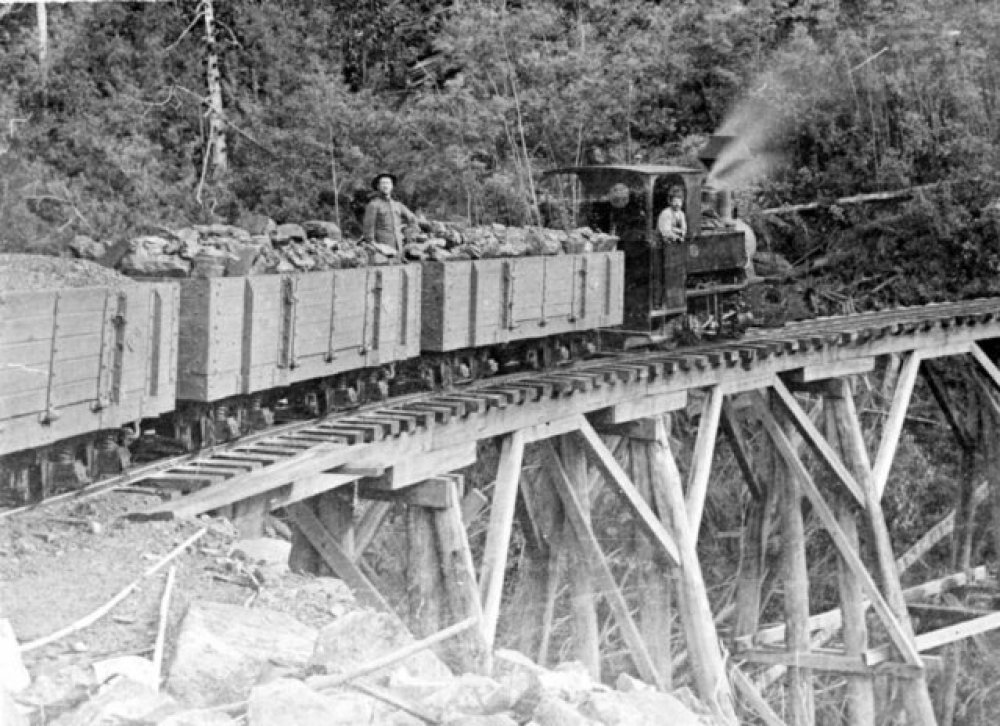 Loaded coal train heading down hill on the Sandfly Colliery Tramway tailed by the 2-4-0T Krauss locomotive. This line ran from coal mines at Kaoota, in the hills around Sandfly, to Margate, south of Hobart on North West Bay, for shipping. Ted Lidster collection via Flickr user Traniac - https://www.flickr.com/photos/29903115@N06/11668439343/in/photostream/