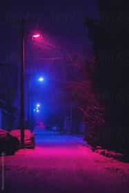 Street at night covered with snow and illuminated with