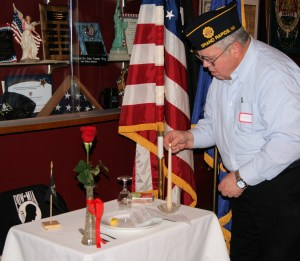 Rick Sturim lighting candle on the POW/MIA Table.