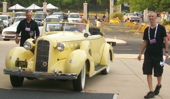 Volunteers escort the first car into position. The 1935 LaSalle owned by Richard Zapalla opened the show.