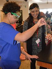 Fifth-grader Samantha Harris works on a chemical reaction with sophomore Maxine Osorio in Accelerated Chemistry class.