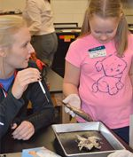 Senior Paige VanderWall shows fifth-grader Vivian Kolkman a frog and fish dissection.