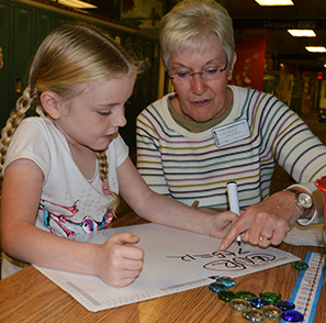 Church member Nancy Heidrich, a retired Grandville High School teacher, helps second-grader Zoey Winship with math