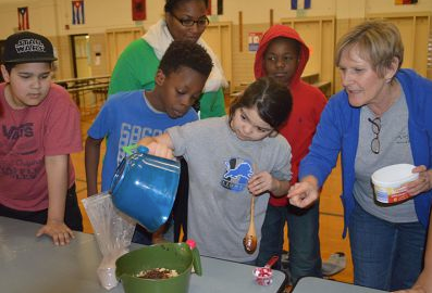 Di Szszesny instructs West Godwin Elementary fourth-graders on coating their treat in melted chocolate