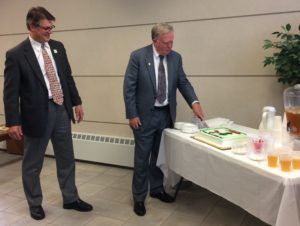 Kentwood District Court Judge William Kelly cuts the cake as former State House Rep. Bill Haveman watches.