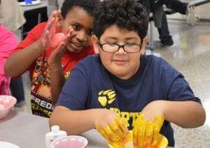 Fifth-grader Sebastion Escalante gets his hands messy while Darryl Jackson watches.