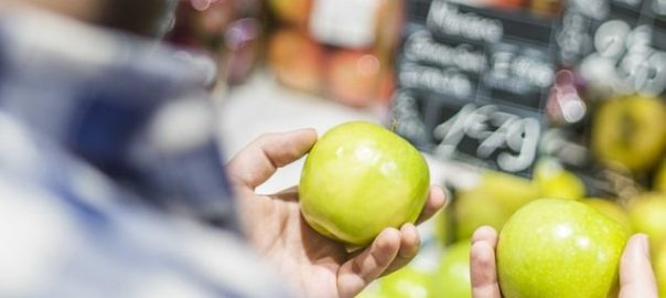 COMPARING A FRUIT showing customer judging the pros and cons of online grocery shopping