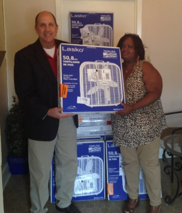Tripp Dungan, Cleco's principal governmental services representative, and Sarah Lloyd, executive director of the Campti Seniors Group, organize 30 fans.