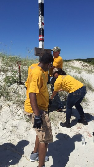 Sailors help move a beach crossing pole to a more visible location.