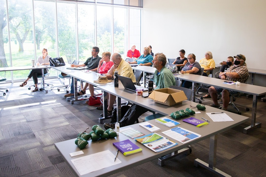 Attendees of the glass recycling meeting sit at tables in the conference room at CCC Hastings Campus