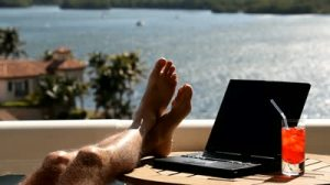 stock-footage-close-up-of-man-s-legs-up-on-a-table-next-to-laptop