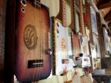 Cigar-box guitars made by a local artist hang for sale in Paints and Pots, an art gallery and shop in Halls Harbour.