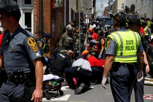 "Rescue workers assist people who were injured when a car drove through a group of counter protestors at the ""Unite the Right"" rally Charlottesville, Virginia, U.S., August 12, 2017."