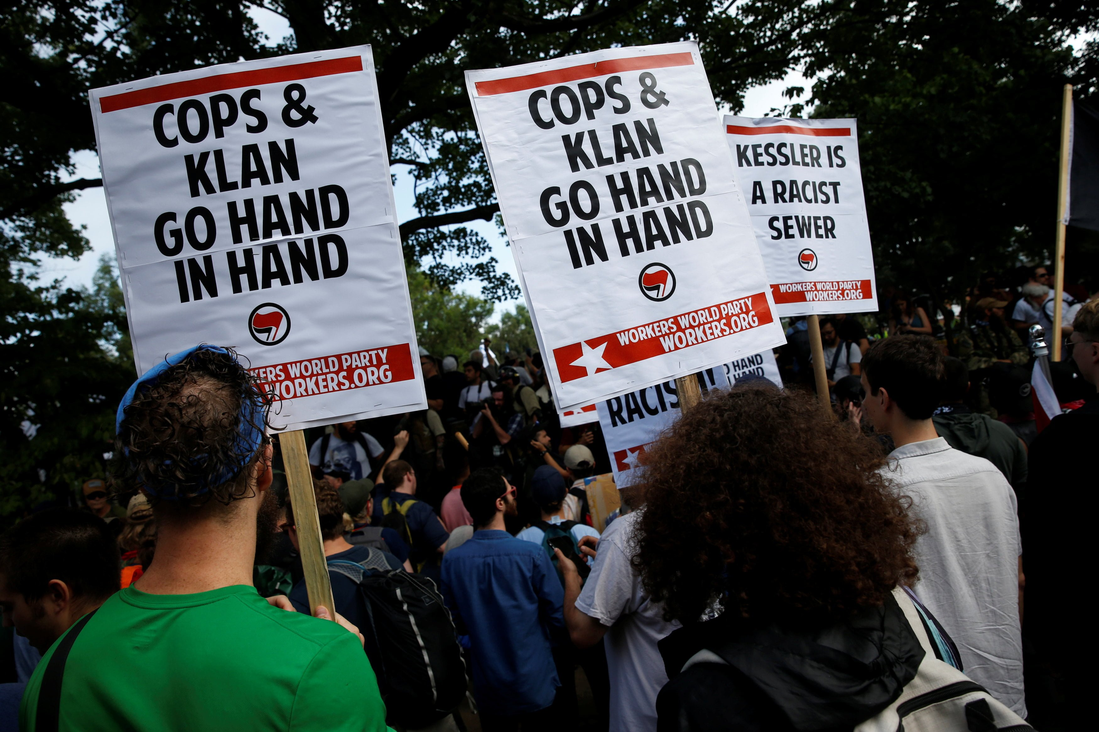 Counter demonstrators carry signs protesting white supremacists and police at a rally in Charlottesville, Virginia