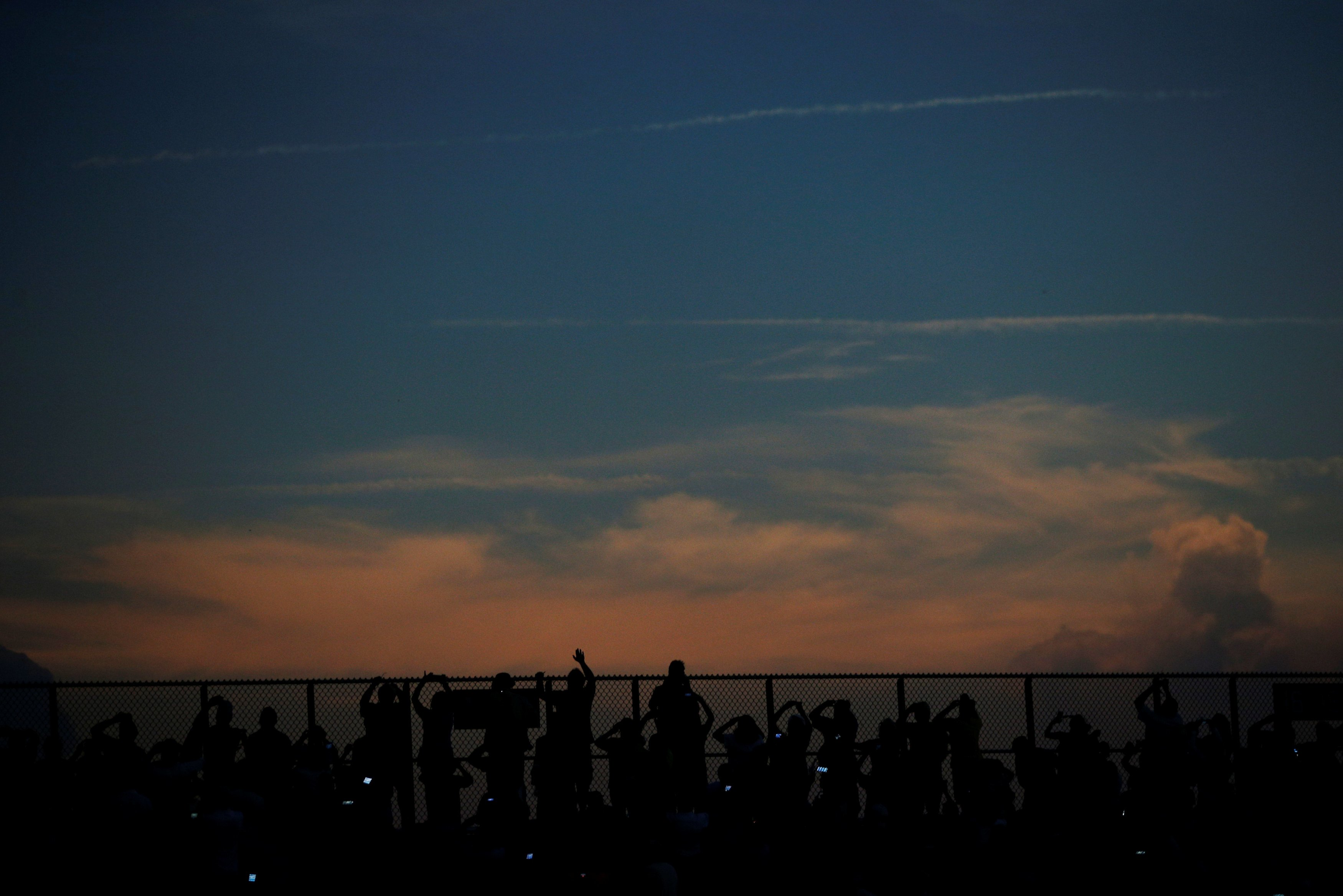 Spectators react to the total eclipse in the football stadium at Southern Illinois University in Carbondale