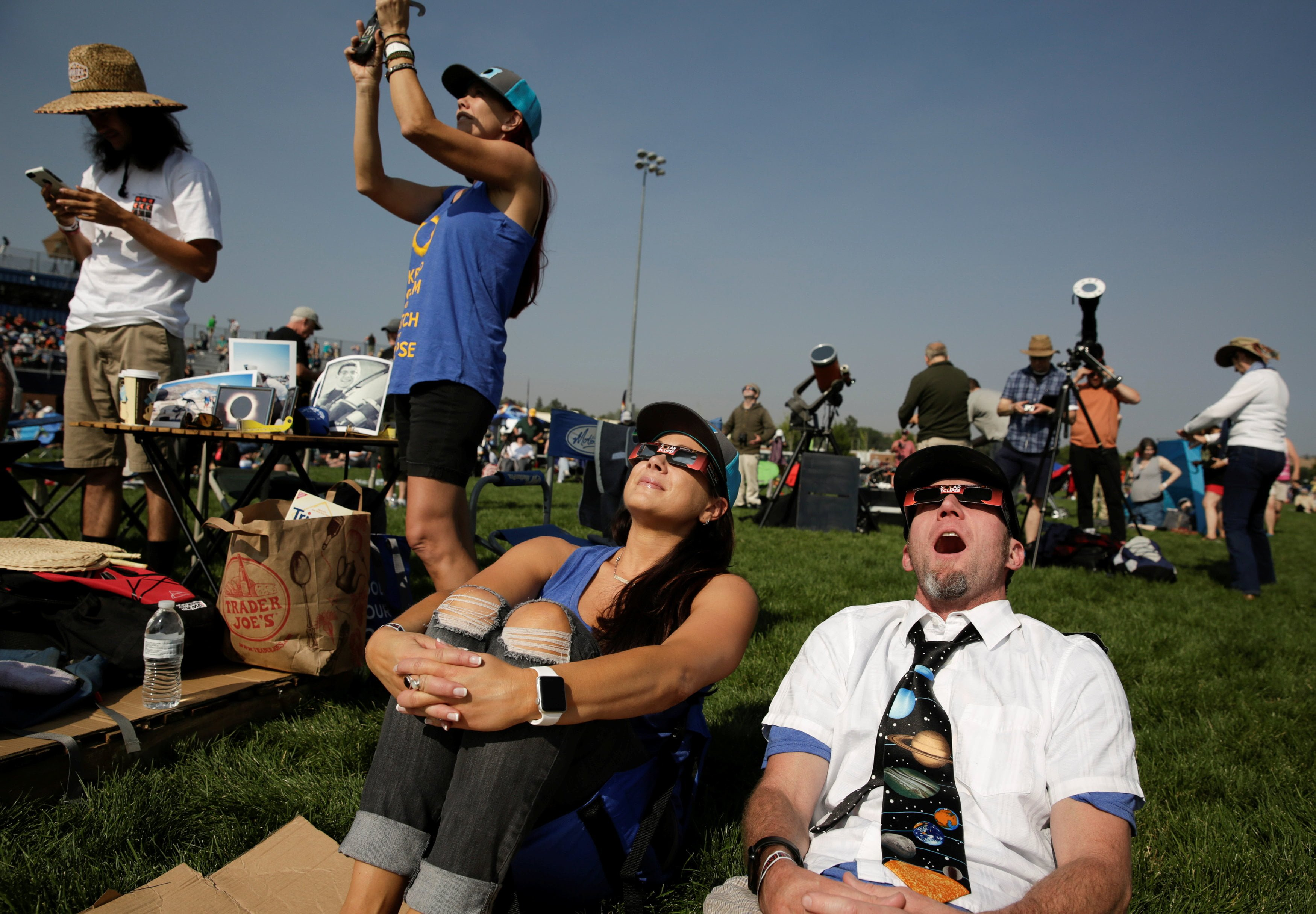 People watch the solar eclipse during the Lowell Observatory Solar Eclipse Experience at Madras High School in Madras, Oregon