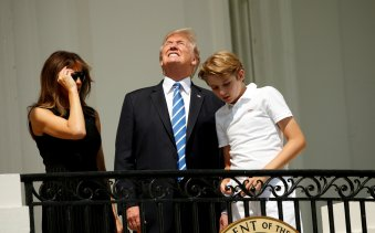 Without his protective glasses on, U.S. President Donald Trump looks up towards the solar eclipse while viewing with his wife Melania and son Barron at the White House in Washington, U.S., August 21, 2017. REUTERS/Kevin Lamarque TPX IMAGES OF THE DAY