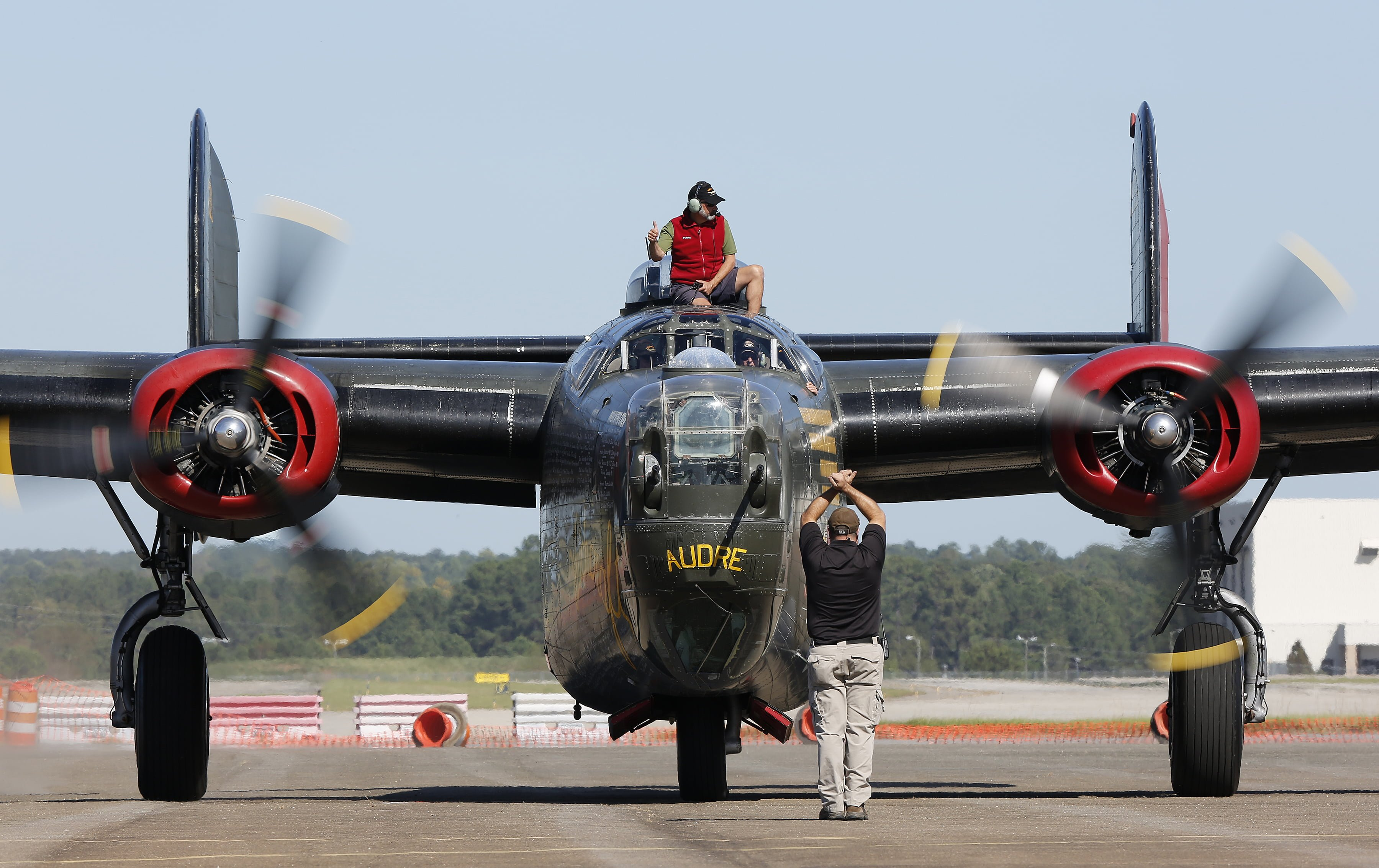 Flight engineer Stephen Arnold, of Seattle, gives a thumbs up as the world's only flying B-24J Liberator comes in for landing at Raleigh-Durham International Airport during the Wings of Freedom Tour, October 19, 2017. Hosted by the Collings Foundation, Wings of Freedom visits more than 100 cities a year to show off working pieces of American war history as well as to educate people about the veterans of WWII. The tour will be in Burlington, NC until 12 pm on Oct. 25 and then move to Statesville, NC through Oct. 27. (Eamon Queeney / North State Journal)