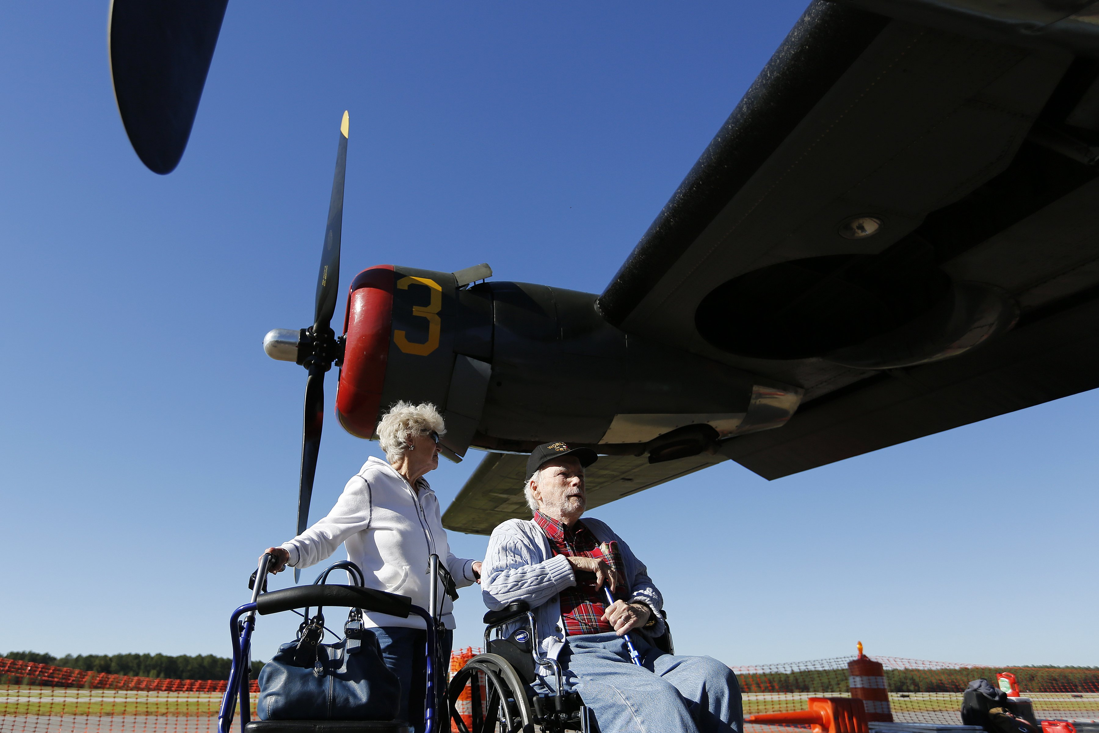 Bob Richeson, 91, of Wilson, NC, talks with his wife Gerry as they examine the world's only flying B-24J Liberator during the Wings of Freedom Tour at Raleigh-Durham International Airport, October 19, 2017. Richeson was a nose gunner in a B-24 in WWII that crashed and was one of only three crew members that survived. He still has trouble talking about the event. Hosted by the Collings Foundation, Wings of Freedom visits more than 100 cities a year to show off working pieces of American war history as well as to educate people about the veterans of WWII. The tour will be in Burlington, NC until 12 pm on Oct. 25 and then move to Statesville, NC through Oct. 27. (Eamon Queeney / North State Journal)