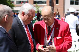 Centennial Commissioner Jerry Hester gives N.C. State Chancellor Randy Woodson a coin on May 1, 2018 in Raleigh. Shawn Krest, North State Journal.