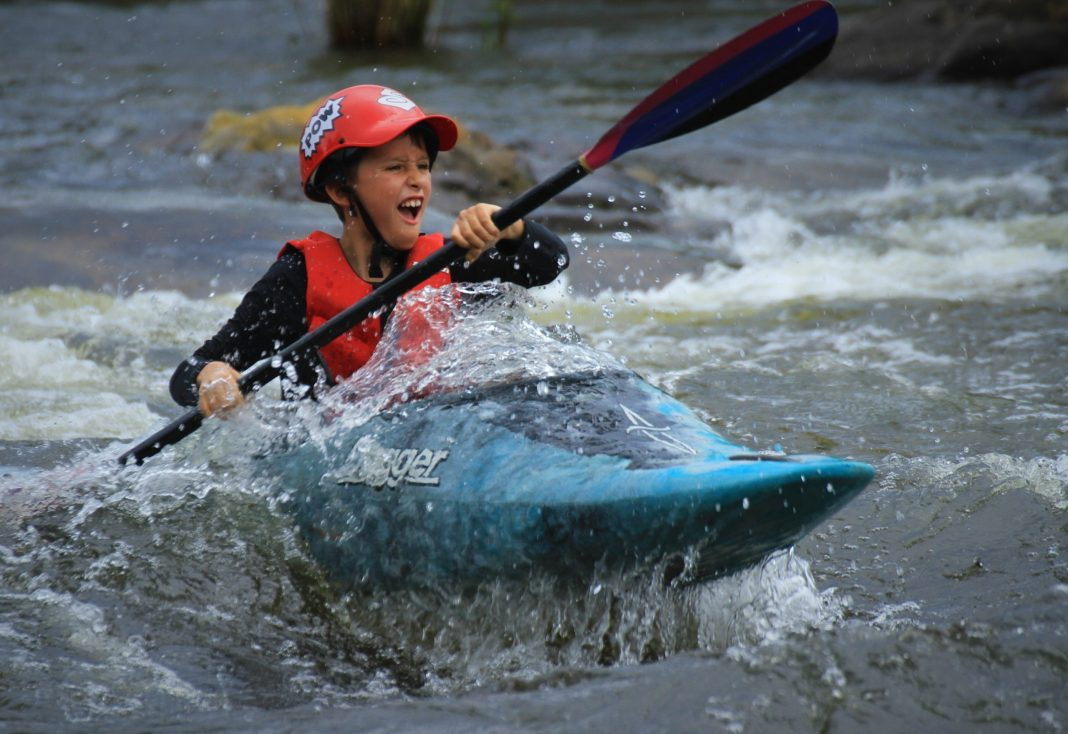 Young paddler in red helmet and blue boat excited to be navigating through whitewater.