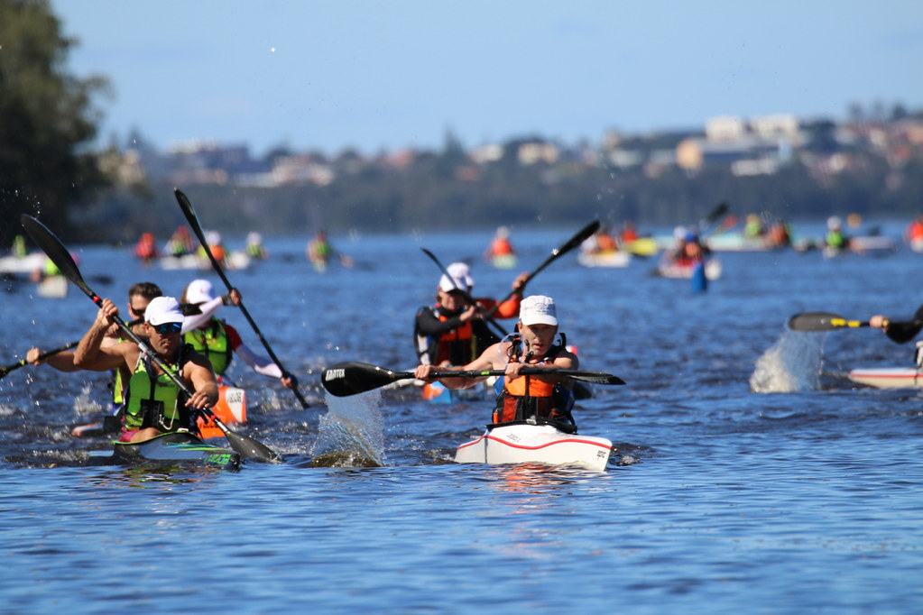 Six paddlers commencing a race, with other paddlers in the background.
