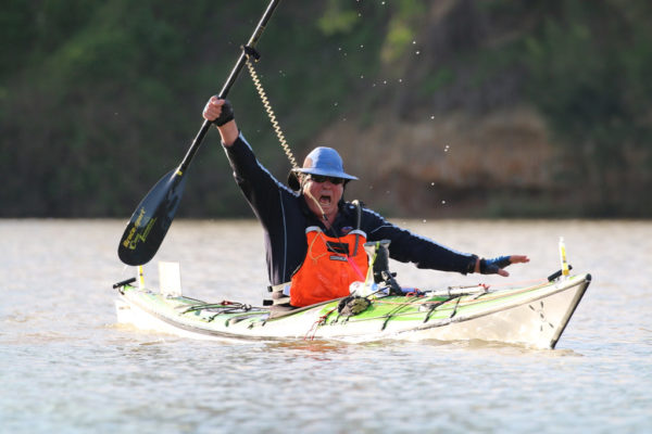 Paddler in single ocean kayak holding paddle up and vocalising in triumph