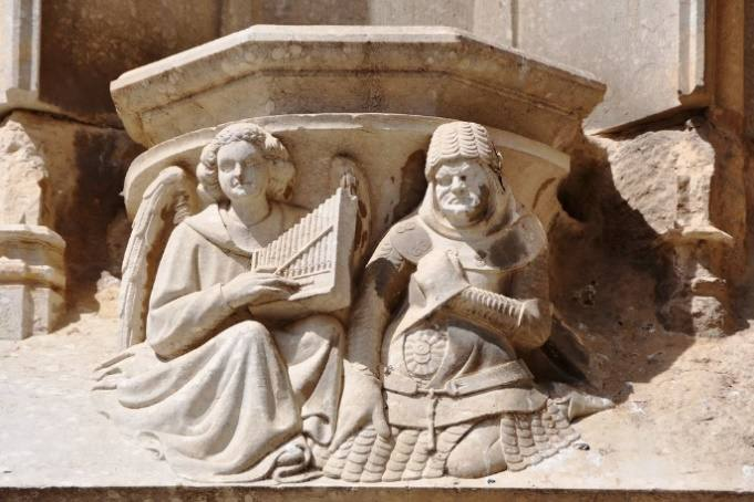 Girona. Cathedral church of Saint Mary. Portal of the apostles. 1370-1382. Corbel. Angel and soldier: the music and the war.