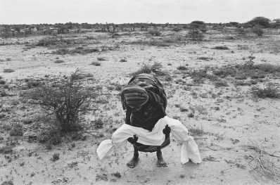 A mother carries her dead child to the grave, after wrapping it in a shroud according to local custom. A bad drought coupled with the effects of civil war caused a terrible famine in Somalia which claimed the lives of between one and two million people over a period of two years, more than 200 a day in the worst affected areas. The international airlift of relief supplies which started in July was hampered by heavily armed gangs of clansmen who looted food storage centers and slowed down the distribution of the supplies by aid organizations. (James Nachtwey)