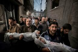 The bodies of two-year-old Suhaib Hijazi and his elder brother Muhammad, almost four, are carried by their uncles to a mosque for their funeral, in Gaza City. (Paul Hansen)