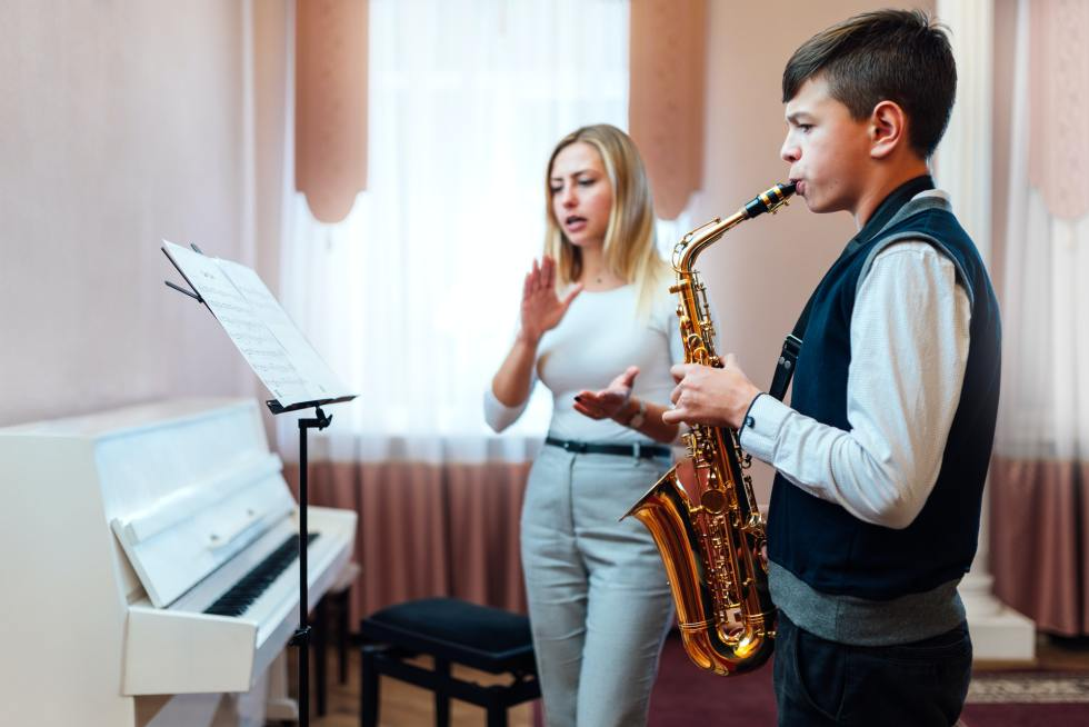 teacher claps for a student on saxophone in music lesson that focuses on playing
