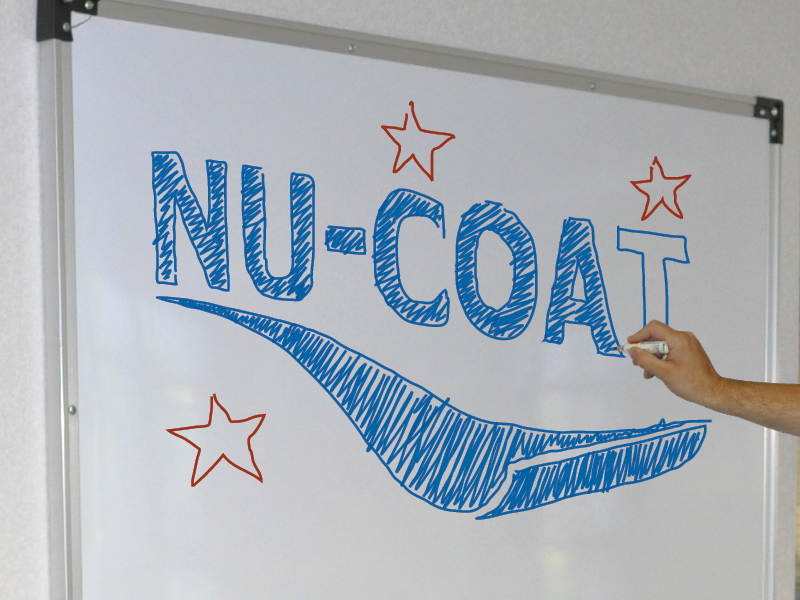Dry-wipe whiteboard laminate film in a silver frame is hung on an office wall and a hand is seen on the right in the process of drawing the NU-COAT logo onto the surface using blue and red coloured dry-wipeboard pens.