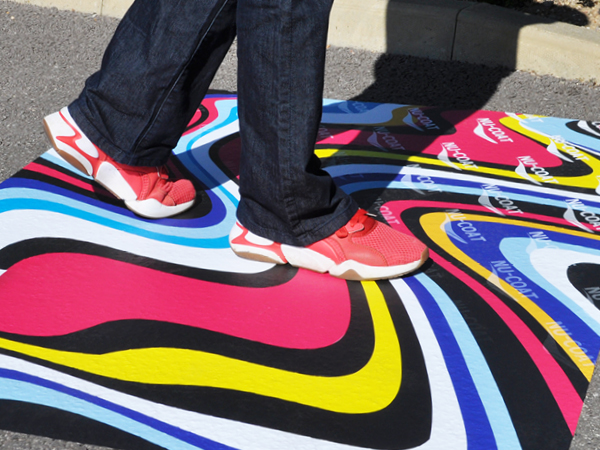 FlooR11 and MaxGRAB print vinyl floor graphic printed with a brightly coloured wavey striped design applied onto an asphalt outdoor surface being walked over.