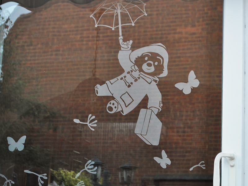Intricate CAD-CUT etch window graphic of Paddington Bear flying through the air surrounded by dandelion seeds and butterflies applied on a garden patio window with the back of the garden and brick wall in the background.