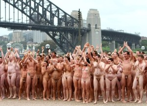 """SYDNEY, AUSTRALIA - MARCH 01: (EDITORS NOTE: Image contains nudity.)Nude members of the public applaud as they notice television reporter Grant Denyer stripping off to take part in """"Mardi Gras: The Base"""", an art installation by artist Spencer Tunick, at the Sydney Opera House on March 1, 2010 in Sydney, Australia. More than 5000 people gathered on a cool, cloudy Sydney morning for Tunick's first Australian installation, which follows visits to the US, Brazil, France, England and Austria. Tunick stated that the title of the work, commissioned by the Sydney Gay and Lesbian Mardi Gras, refers to the sameness of individuals, regardless of their sexual preferences. (Photo by Don Arnold/WireImage)"""