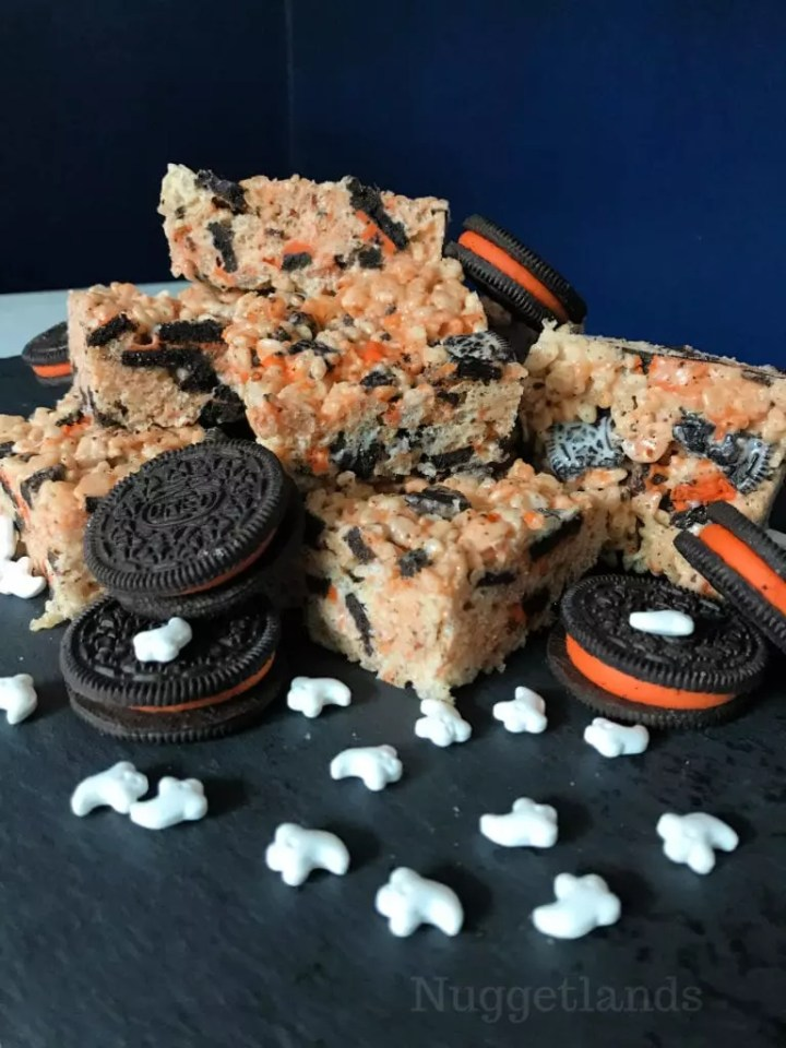 Halloween Rice Krispie Treats that are easy to make and fun for kids. Lots of ideas on how to serve them either in squares on a stick or festive shapes like ghosts and pumpkins. This fun recipe uses Oreos for the orange and black color pop. #halloween #RiceKrispie #treats #sweets #dessert #onastick #recipe