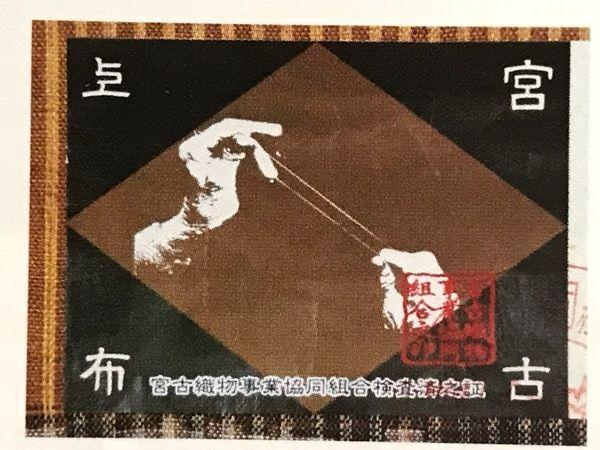 宮古織物事業協同組合による草木染の宮古上布に貼られる証紙