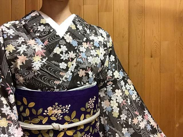 桜楓文様の小紋と紫地の変わり絽の萩文様の名古屋帯のコーディネートの装い