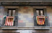 Flags that represent Catalonia and Barcelona hang off a building on the edge of the Gothic Quarter in Barcelona.