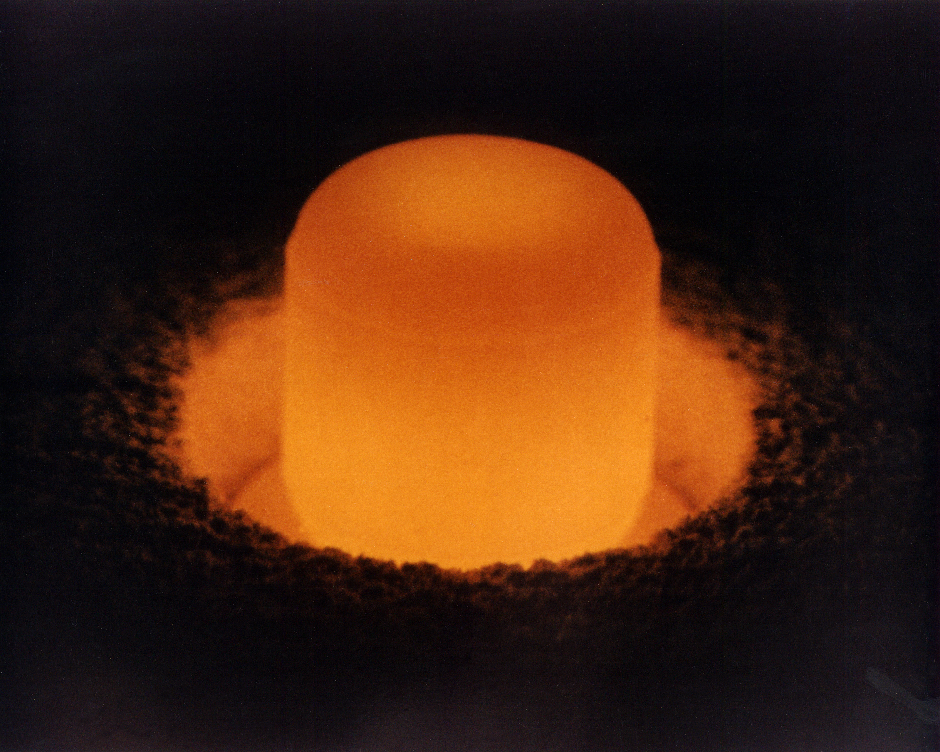 Glowing cylinder of plutonium oxide standing in a circular pit