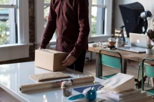 A man packing a small crate at a busy desk. Local movers Hamilton will handle your packages gently!