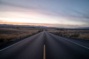 A long stretch of an empty country road during daybreak.