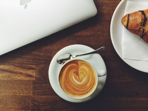 A coffee with a laptop and croissant almost out of view, in the corners. One of the top things to do in Hamilton is to take in the atmosphere downtown from one of the cafés.