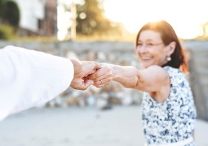An older lady holding a mans hand in what appears to be a dancing motion.