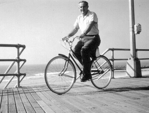 the father cycling on boardwalk